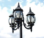 Lamp post with three lights. Lamp post with three lamps with energy efficient compact fluorescent bulbs Stock Photo