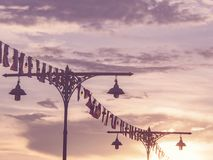 Lamp posts with colorful light bulbs and flags. Classic Thai lamp posts with colorful light bulbs and flags for festival over dramatic sky at sunset, vintage Royalty Free Stock Photo