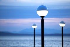 Lamp posts lit at night, blue mountains at dusk. Lamp posts lit at night with blue mountain background and lake scene at dusk Royalty Free Stock Image