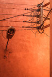 Lamp with power supply lines. On a beautfully lit orange wall Royalty Free Stock Image