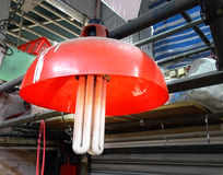 Lamp with red lampshade and huge energy saving lamp Stock Photos