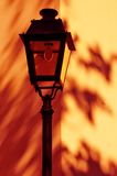 Lamp with Red shadows. Street lamp in front of yellow wall with red shadows on the wall Royalty Free Stock Photo