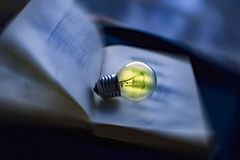 lamp rests on an open book, knowledge is light Royalty Free Stock Images
