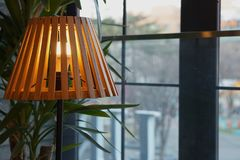 The lamp in romance background. The beautiful wood light lamp in romance window view background with small tree behind Royalty Free Stock Image