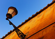 Lamp in Rome's centre. A lamp, a colourful wall and a blue sky in Rome's centre Royalty Free Stock Images