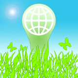 Lamp Saving Life. Green saving lamp with globe symbol inside bulb between green grass and butterflies over blue sky background with sun Stock Photography