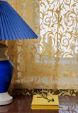 The lamp with shade, a book and a window with a curtain. Blue and yellow Stock Photography