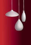 Lamp shades. Three lamp shades on a maroon background Royalty Free Stock Photos