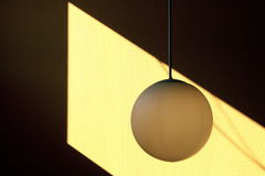 Lamp and shadow. A lamp hanging down from the roof in i sunlit space on the wall stock photos