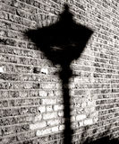 Lamp Shadow. Shadow of a old street lamp on brick wall stock photo