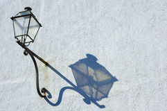 Lamp and shadow. An antique street lamp, on a rusting iron support, casts its shadow in the afternoon sun. Rust stains on the wall. Space for text Stock Photo