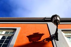 A lamp and a shadow in Tenerife. The shadow of an old street lamp with an orange wall and a blue sky Royalty Free Stock Images