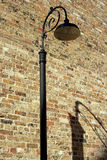 Lamp and shadow. A street lamp against a brick wall and its shadow aside Royalty Free Stock Images