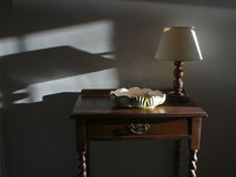 Lamp and shadow on wall. Shadow play with cabinet lamp and old bowl Stock Image