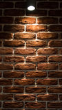 The lamp shines on the wall. The lamp weakly shines on the brick wall Royalty Free Stock Images