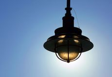 Lamp Silhouette. Exterior light fixture silhouetted against the sun royalty free stock images