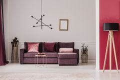 Lamp in sophisticated living room. Wooden lamp against red wall in sophisticated living room interior with violet corner couch Stock Photo