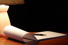 Lamp And Spiral Notebook Royalty Free Stock Photography