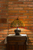 Lamp of stained-glass on red brick wall. Table lamp of stained-glass on old wooden stand on red brick wall background royalty free stock image