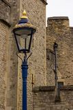 A lamp stands out in gold and blue splendor against dull stonework of medieval fortifications. As a drainpipe makes its way down the wall in the background Stock Image