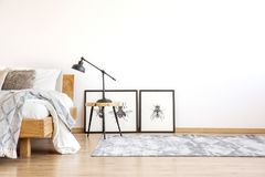 Lamp on stool in bedroom. Lamp on stool next to bed in bright bedroom with copy space on white wall and posters on the floor stock image