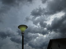 Lamp and storm. End of the manufacture of incandescent bulbs concept. urban electric light pole in the background a nearby tropical storm with several high and Royalty Free Stock Photography