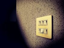 Lamp Switch on wall, under light and shadow. Picture with copy space Royalty Free Stock Photography