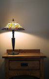 Lamp on table. Lamp with stained glass shade on wooden table Royalty Free Stock Photography