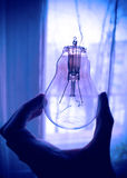 Lamp in hand with a torn spiral Stock Images