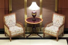 A lamp between two luxurious chairs Royalty Free Stock Images