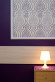 A lamp with violet wallpaper. A lit bedside lamp with violet theme decorative wallpaper Royalty Free Stock Photography
