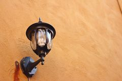 A lamp on a wall on brown background. Royalty Free Stock Image