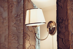 Lamp on the wall. Lamp on a wall with curtains Stock Images