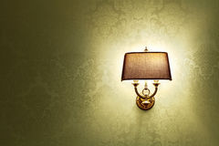 Lamp. Wall lamp with a shade on the background of Golden Wallpaper Royalty Free Stock Photography