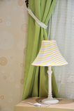 Lamp and window curtain. Lamp yellow color cover on small wooden table, beside light green and white window curtain and light color wallpaper, shown as room Royalty Free Stock Photos