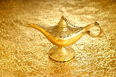 Lamp of wishes - Aladdin lamp on a golden background.