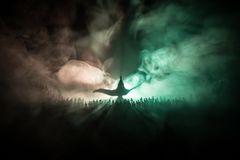Lamp of wishes. Silhouette of a large crowd of people standing against a big lamp of wishes with toned light beams on foggy backgr. Ound. Dark night table royalty free stock photography