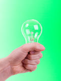 Lamp in a woman's hand. On green background Royalty Free Stock Photography
