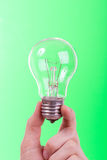 Lamp in a woman's hand. On green background Royalty Free Stock Photo