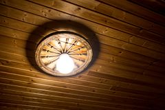 Lamp on a wooden ceiling. In the house Royalty Free Stock Photo