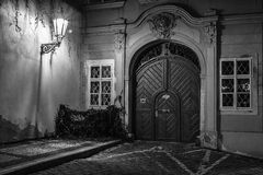 Lamp and a wooden doors. In dark street in black & white design Stock Images
