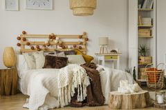 Boho style bedroom interior. Lamp on wooden stool next to bed with cotton balls and knit blanket on bed in boho style bedroom interior stock images