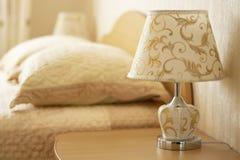 Lampa för att läsa på en nattduksbord mot bakgrunden av en hemtrevlig inre av sovrummet Selektivt fokusera royaltyfri bild