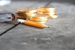 lampa för idé för sedelkulaaffär över Blyertspenna med text och guld- mynt Arkivbilder