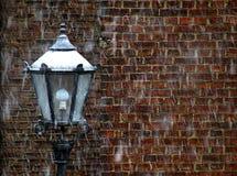Lampa framme av en vägg med att snöa bakgrund arkivbilder
