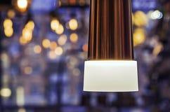 Lampa med vitt frostat exponeringsglas på en blå bakgrund med bokeh fotografering för bildbyråer