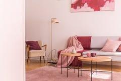 Lampa mellan fåtöljen och soffan med den rosa och röda filten i plan inre med tabeller Verkligt foto royaltyfria bilder