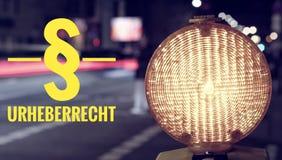Lampa och trafik för konstruktionsplats på natten med inskriften i tysk § Urheberrecht i engelsk förklaring av copyrighten royaltyfria foton