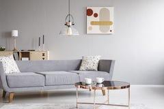 Lampa ovanför grå färgsoffa med kuddar i ljus vardagsruminre med affischen och tabellen Verkligt foto royaltyfria bilder
