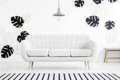 Lampa ovanför soffan i den vita vardagsruminre med randig carpe royaltyfri bild